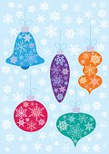 Orange, blue, red, aquamarine and violet Christmas baubles on the light blue background with white snowflakes