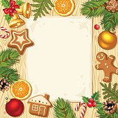 Christmas card with fir-branches, balls and cookies on wooden background.