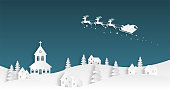 Christmas celebration. Santa Claus flying in the sky over village in paper cut style. Digital craft paper art background.
