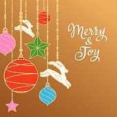 Celebrate the Christmas with colorful ornaments including stars, baubles and reindeers hanging on gold colored background