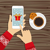 istock Christmas gift on smart phone screen and coffee with cookie 1204767558