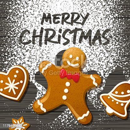 Gingerbread cookies of man, heart, bell and star put on the background of powdered sugar spreading over the black wooden table