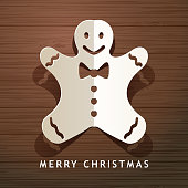 Celebrate Christmas with paper craft of folded Christmas gingerbread man on the wood table background