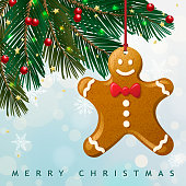 Christmas gingerbread man hanging on the Christmas tree with the snowy background