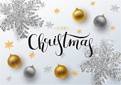 Christmas greeting card,  vector background.Gold and silver Christmas ball, with an ornament and spangles. Metallic gold and silver Christmas snowflake. Hand drawn lettering. Vector illustration