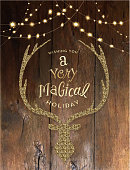 Vector illustration of a Christmas greeting string lights with deer head and antlers design with hand drawn text. On rustic wooden background.