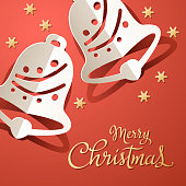 Celebrate Christmas with paper craft of gold colored stars and folded jingle bells on the metallic red colored background