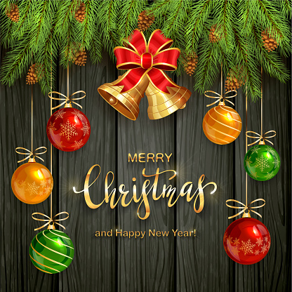 Christmas Lettering on Black Wooden Background with Golden Bells and Balls