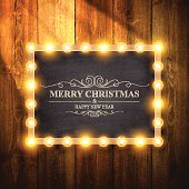 Christmas background . Christmas Lights on chalkboard and wooden wall.