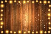Christmas lights on Realistic blank wooden wall with falling snow.