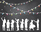 Large group of kids on a chalkboard background with colorful christmas lights