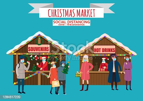 istock Christmas Market holiday fairs or festive on city square. In conditions of the COVID 2019 pandemic sellers in medical masks, Social distancing. People walk and buy between canopy, stalls souvenirs hot drinks. Background silhoutte old town 1284517220