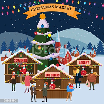 istock Christmas Market holiday fairs or festive on city square. In conditions of the COVID 2019 pandemic sellers in medical masks, Social distancing. People walk and buy between canopy, stalls, kiosks canopy, stalls, kiosks. Background silhoutte old tow 1286084801