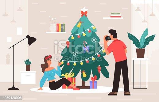 istock Christmas photo session, cartoon photographer photographing beautiful girl next to Christmas tree 1280426906