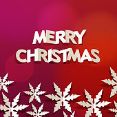 Celebrate Christmas with paper craft of snowflakes and folded English alphabets on the red background
