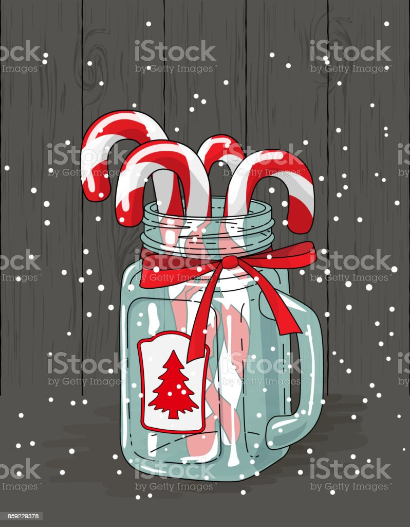 christmas theme candy canes in glass jar with red ribbon