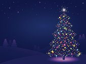Christmas tree background - snowy winter scene at twilight with a Christmas tree with coloured lights.