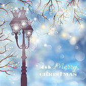 Christmas vintage card with street lamp at night on defocused background
