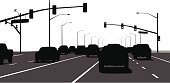 A vector silhouette illustration of traffic on a busy road going through an intersection.