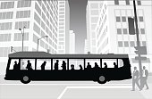 A vector silhouette illustration of a city bus with passengers traveling through an intersection, and tall office buildings.