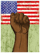 istock A clenched African-American fist against a US flag with a grunge texture. illustration 1253501444