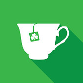 Vector illustration of a white tea cup with a clover clef teabag on a green background.