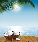 Two coconut halves on a table in front of a tropical ocean with bright reflections and palmleaves. EPS10 file with transparencies (sun) and shine effect in the reflections of the ocean. Layered file and grouped elements. Included: EPS10, AI10 and large JPG (42cm high, 300dpi)