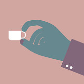 Coffee cup in the hand. Isolated on brown background.