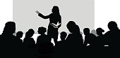 A vector silhouette illustration of a female professor giving a lecture to a lecture hall of college students.