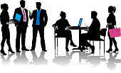A vector silhouette illustration of modern business meeting with business men and women.  A group of two men and one woman stand and talk while the young woman holds a lap top.  A man and woman sit at a desk approached by another young woman with a pink purse.