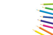 Colored pencils located on the edge of page with copy space for note, text, on white background. Rainbow colors. Bright print. Page for notebook