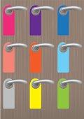Colorful blank door hangers on door knobs