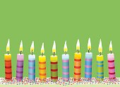 Colorful burning candle on green background