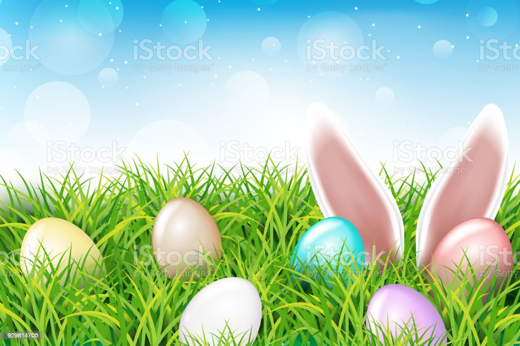 colorful easter eggs and rabbit ears sticking out of the grass