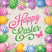 Colourful Easter eggs with coloured eggs, butterfly, daisies, wooden background and text Happy Easter.