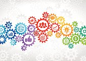 Multi colored connected gears with icons in it symbolizing business strategy, success, teamwork, communication concepts. In the background is gray halftone and gray gears.
