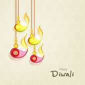 Colorful hanging lit lamps on seamless floral patterned abstract background for Happy Diwali festival celebrations.