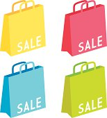 Sale labels on different colored goodie bags.