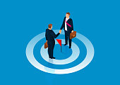 Common goal, reach agreement, two businessmen stand on the bullseye and shake hands