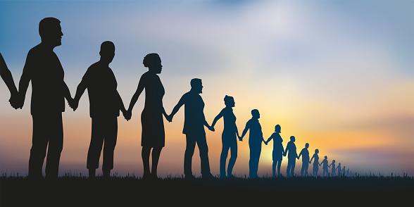 Concept de la chaîne humaine et de la solidarité avec un groupe de personnes alignées qui se donnent la main pour montrer que l'union fait la force.