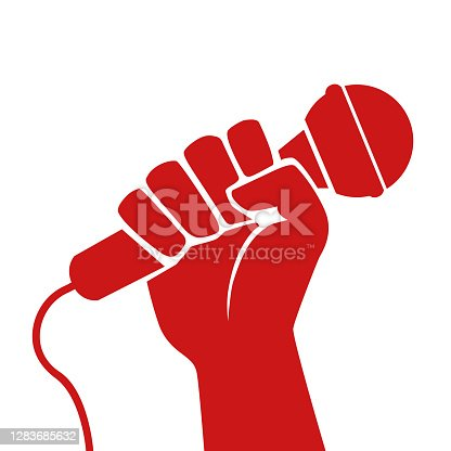 istock Concept of the fight for freedom of information with a raised fist holding a microphone. 1283685632