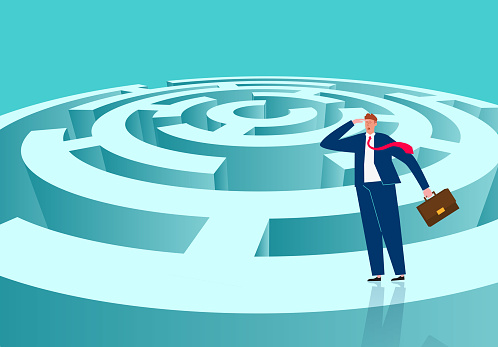 Conceptual illustration of businessman standing at the top of the maze trying to find a way to reach the goal through the maze and striving to achieve the business goal