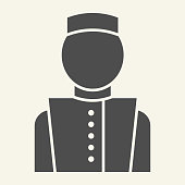 istock Concierge solid icon. Hotel porter symbol, glyph style pictogram on beige background. Bellboy in uniform sign for mobile concept and web design. Vector graphics. 1223191849