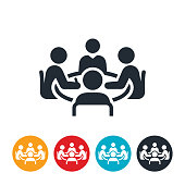 An icon of a conference room meeting. Four business people sit around a conference table as part of the meeting.
