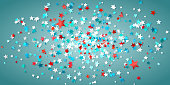 Multi colored star shaped confetti on blue background.