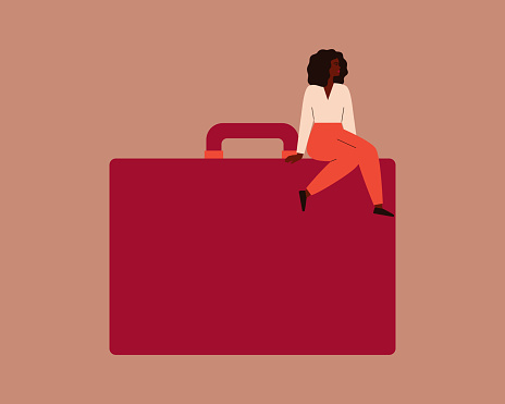 Confident black businesswoman sits on a large red briefcase.