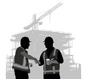 A vector silhouette illustration of two construction workers shaking hands and holding coffee cups wearing hard hats and safety vests standing infront of a building being constructed.