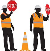 Vector silhouette of a construction worker wearing a reflective vest and a holding stop sign standing next to an orange safety cone.