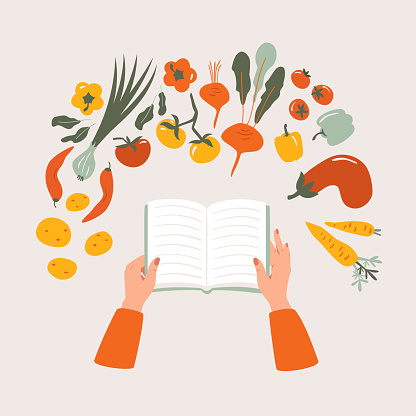 cookbook in hand on the table surrounded by various vegetables