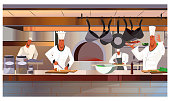 Cooks working at restaurant kitchen vector illustration. Busy chefs in uniform cooking dishes. Restaurant staff concept